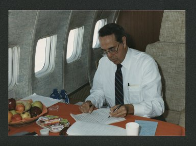 Bob Dole proofreading documents during Japan trip, 1985